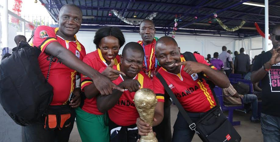 KCCA FC chairman Julius Kabugo (2nd R) and board member Ali kasirye Nganda Mulyanyama with other Uganda Cranes fans pose with a dummy AFCON trophy moments after they arrived at Port Gentil