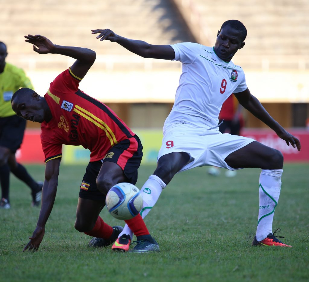 KCCA FC Striker Geoffrey Sserunkuuma (L) battles for possession with Kenya's midfielder Anthony Akumu at Namboole in an international friendly.